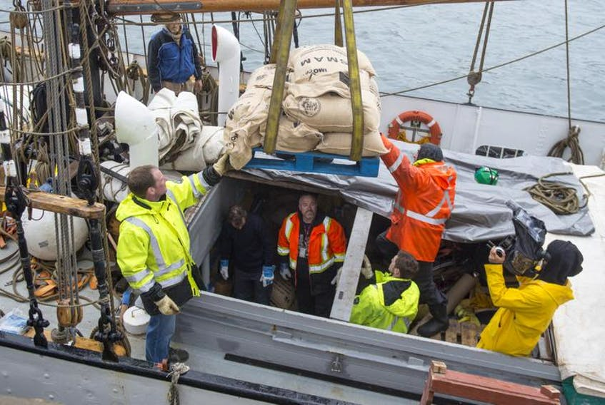 A pallet of sacks filled with coffee beans is hoisted from the cargo hold of Avontuur, a two-masted schooner docked in Halifax. The cargo for Just Us Coffee Cooperative in Grand Pré was unloaded Wednesday by members of the Halifax Longshoremen's Association Local 269, who volunteered their time.