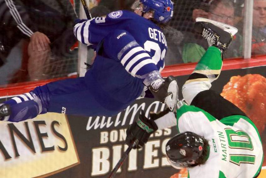 Halifax Mooseheads' Keith Getson, left, and Prince Albert Raiders' Max Martin go flying after a major collision behind the Halifax net in the first period of the opening game in the Memorial Cup on Friday at Scotiabank Centre.