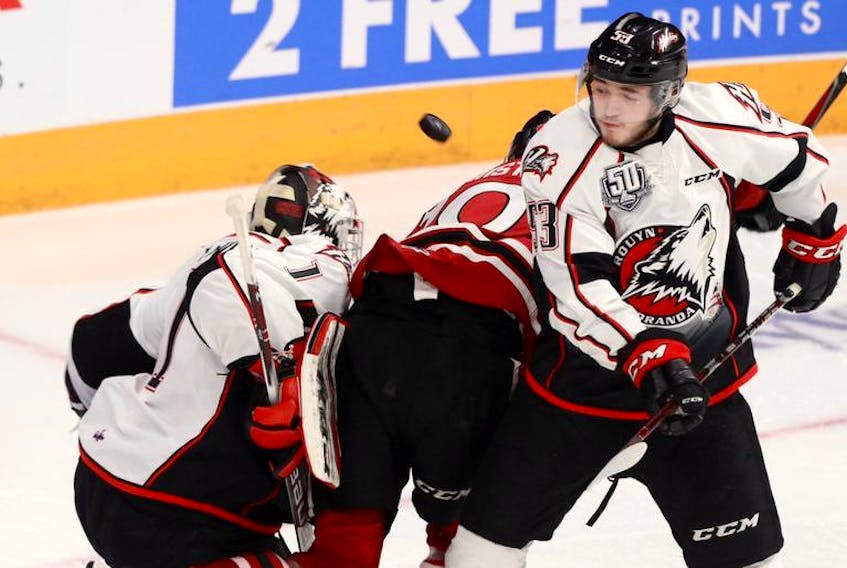 Rouyn-Noranda Huskies defenceman Noah Dobson and goalie Samuel Harvey track the flying puck during Saturday's Memorial Cup game against the Guelph Storm at the Scotiabank Centre.