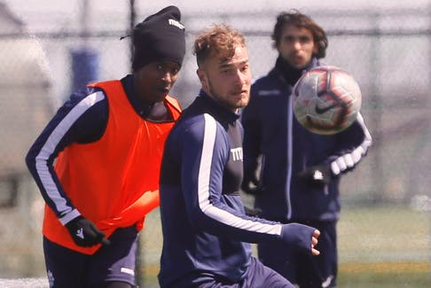 HFX Wanderers FC defender Peter Schaale, middle, defends against teammate Abd-Al-Aziz Yousef, left, during a team practice at the Mainland Common in Halifax on Thursday. The Canadian Premier League team will play its first home game on Saturday against Forge FC of Hamilton at the Wanderers Grounds at 2 p.m.