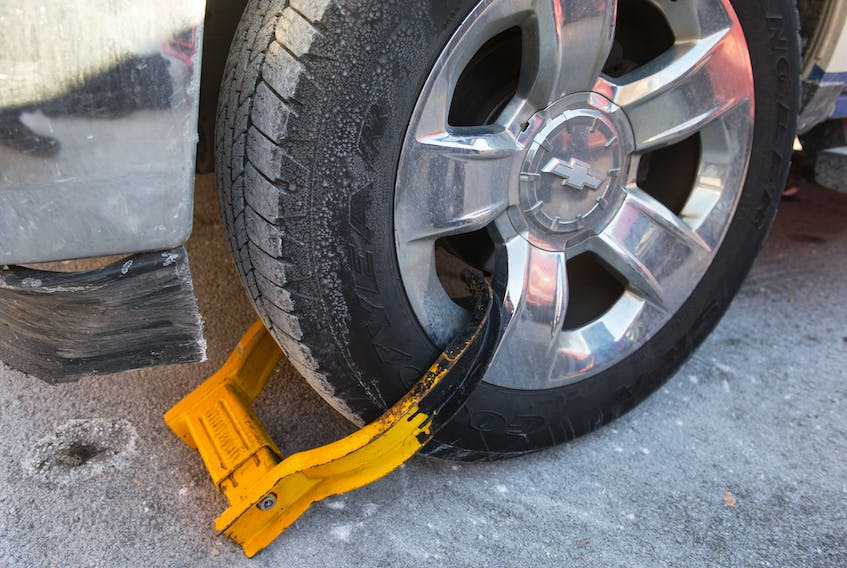 A parking boot is locked on a truck's wheel in a downtown Halifax parking lot.