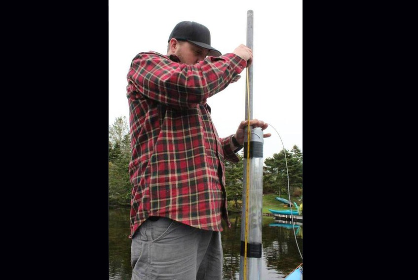 Bishop's University student Frank Oliva handles a sediment core while assisting the research project conducted by Matthew Peros in Nova Scotia.