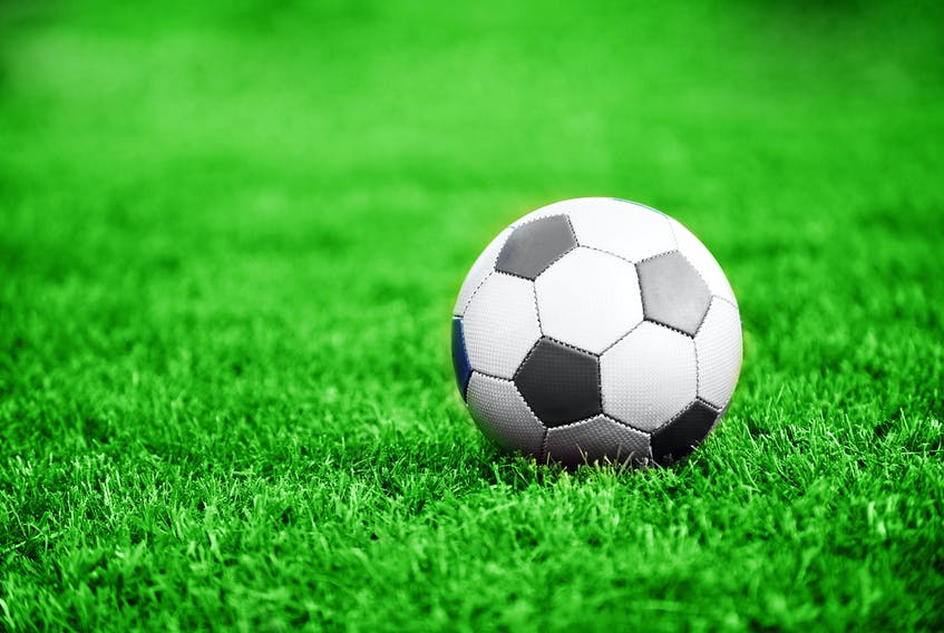 A soccer ball sits on a pitch.