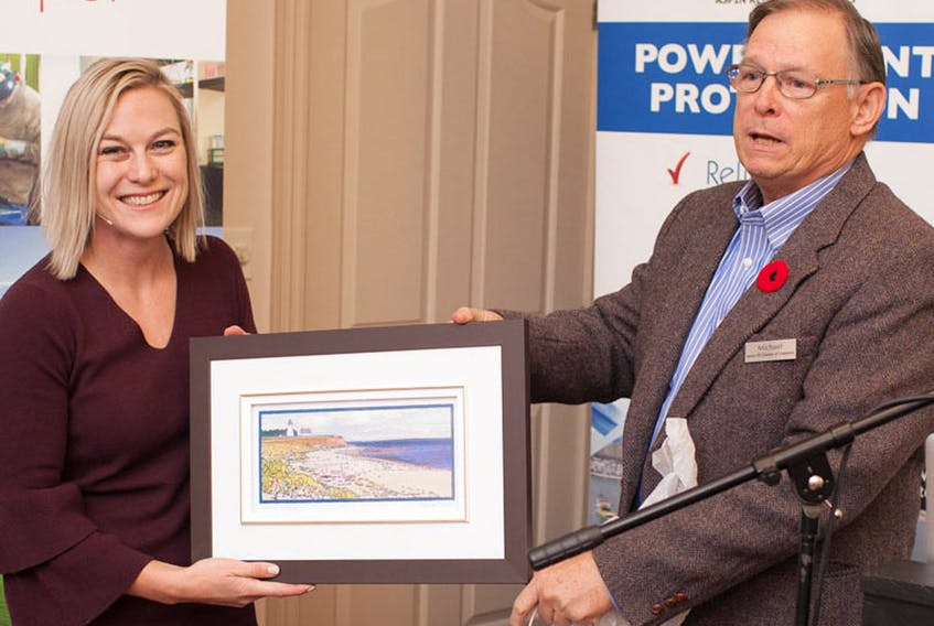 Nicole Verkindt, founder and CEO of OMX (market exchange) is presented with a gift from Michael Shumate, secretary of the Eastern P.E.I. Chamber of Commerce. Verkindt was the keynote speaker at the chamber's recent conference. SUBMITTED PHOTO