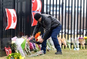 A member of the Veterans Canada motorcycle group leaves a riding bandana at a makeshift memorial to Nova Scotia shooting victims outside the Nova Scotia RCMP headquarters in Burnside Monday afternoon, April 20, 2020.