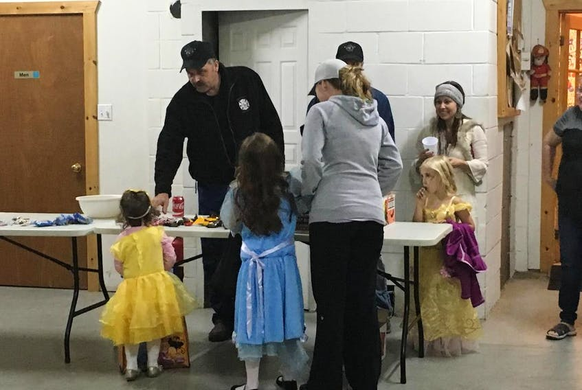 Fire Chief Kevin Sprague hands out treats to (behind table) Ellie MacLeod with parents Cecil MacLeod and Stacie MacLeod, and to (backs to camera and in front of table) Taylor Flanagan and Maddy Flanagan, with mother Melissa Flanagan.