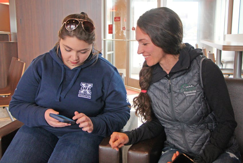 Friends Kendra Vigneau, left, and Kaitlin Knox look at photos from a recent fundraiser they led, which sent veterinary medical supplies to Australia for animals affected by continuing wildfires. Corey LeBlanc
