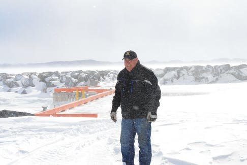 Wallace Gillard steps out to the new Gillard's Cove wharf on a windy and snowy morning.