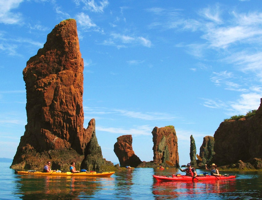 Kayakers with NovaShores Sea Kayaking pass the iconic Three Sisters sea stacks formation in Cape Chignecto Provincial Park. - Contributed