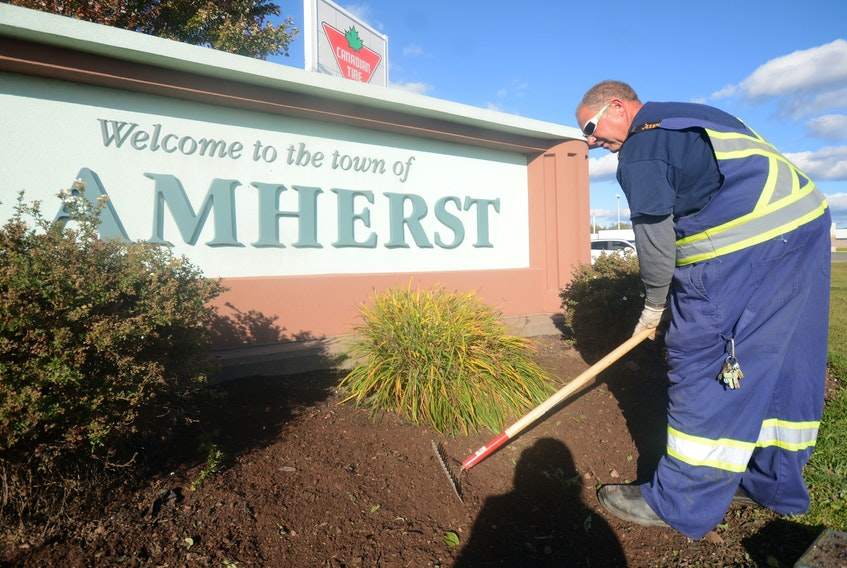 After pulling annual flowers out of the ground, which will be stored away until next spring, Vaughn Martin, an employee with the Town of Amherst, rakes the flower bed at the entrance to Amherst.