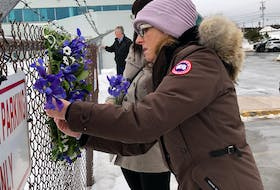 Lori Chynn of Deer Lake, whose husband John Pelley was lost in the Cougar Helicopters Flight 491 tragedy, places her tribute to him at the makeshift memorial on the chain-link fence outside the former Cougar Helicopters building at St. John's International Airport this morning. Standing next to her is Julie Marsh of Torbay whose brother-in-law Corey Eddy of Sibley's Cove, T.B., was also lost in the accident. Joe Gibbons/The Telegram