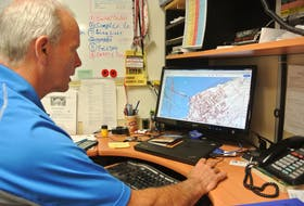 Mike Johnson, Cumberland County's EMO co-ordinator, looks over maps of the potential flood risk to areas of the county around the Tantramar Marsh and the Bay of Fundy that could be impacted by sea level rise or a significant storm that breaches the dikes. Johnson will be going door-to-door collecting phone numbers and email addresses to put into a mass notification system should the need arise to quickly alert residents and business owners in the affected areas.