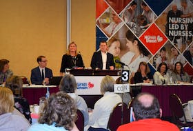 Nova Scotia Nurses Union president Janet Hazelton is seen sharing the microphone with Health and Wellness Minister Randy Delorey during the union's annual conference in Truro on Monday.