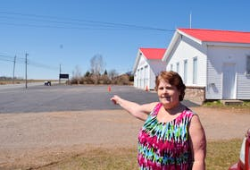 Joy McCabe of Lower Onslow points out towards a wooden garbage bin at the edge of the Onslow Belmont Fire Hall parking lot. That is where she says two RCMP officers crouched behind after firing off a number of rounds at an unidentified target, during the period when the Portapique shooter was on the loose. She later learned the shooter had already passed through the area by that point.