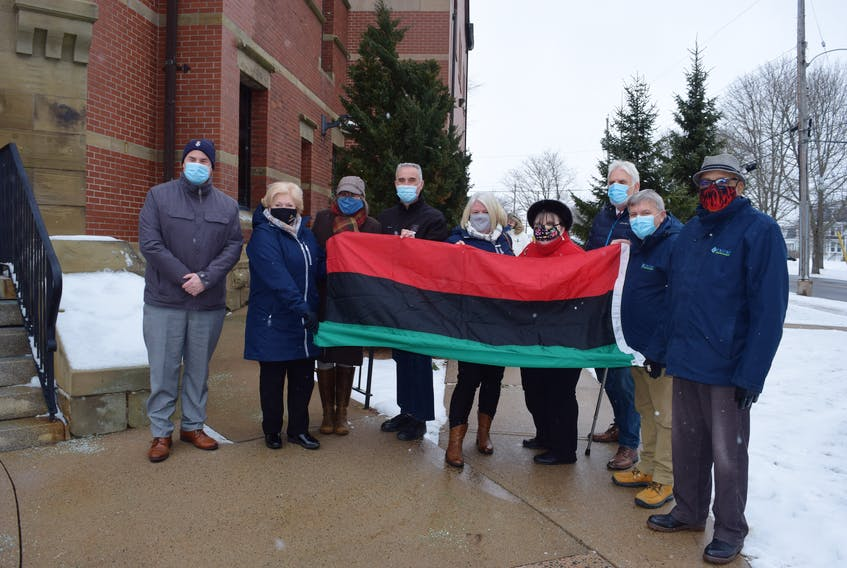 Town and county representatives gather around the Pan-African flag.