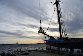 Laurie Macdonald gets hoisted to the Hector's mast. All the ropes fixed to the masts must be removed before the crane can lift these important 1500 pound wooden poles can be taken off the deck.