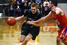 Carter Brown of the Breton Education Centre Bears, left, works his way to the basketball as he's pressured by Tie Dewacht of the Winston Churchill Bulldogs during New Waterford Coal Bowl Classic action at the Breton Education Centre gym on Tuesday. Winston Churchill won the game 77-75.