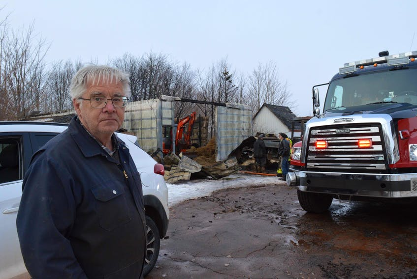 Farmer Leonard Malone stands in front of his destroyed barn. He had just put away his tractor and gone for the mail when the fire broke out 9:30 Wednesday morning. None of his beef cattle were harmed.