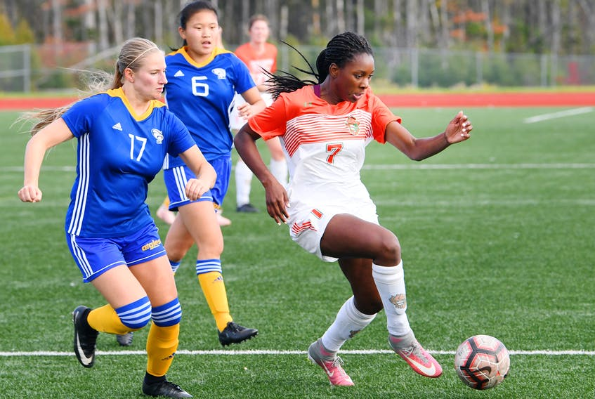 Fatou Ndiaye of the Cape Breton Capers, right, carries the ball while being pressured by Madelaine Leblanc of the Moncton Aigles Bleus during Atlantic University Sport women's soccer action at the Cape Breton Health Recreation Complex in Sydney. Cape Breton won the game 6-1.