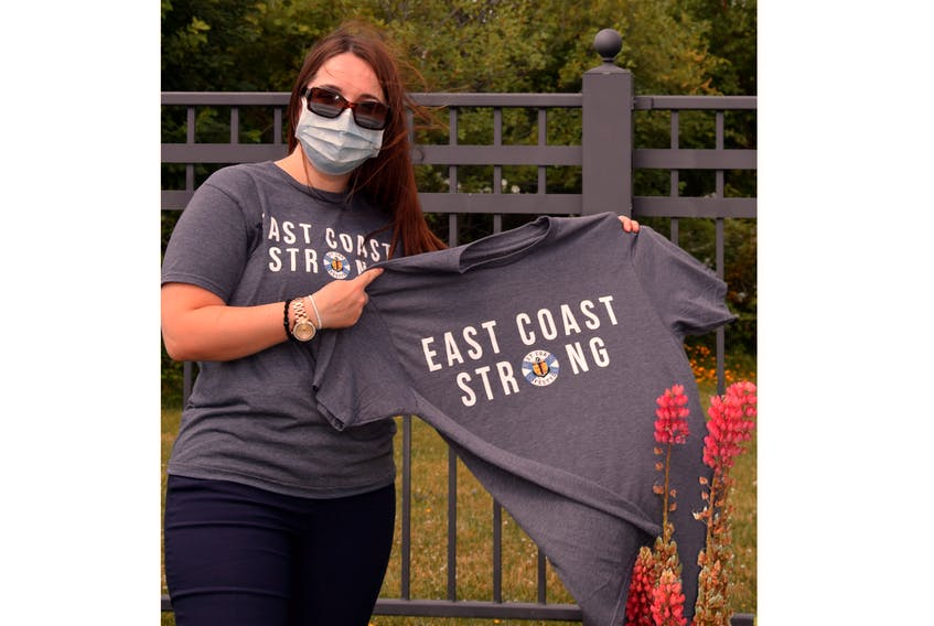 Amanda DeCoste, finance associate at Glen Haven Manor is pictured among iconic Nova Scotia lupins in the Amirah Garden at Glen Haven Manor as she shows the East Coast Strong t-shirts that Glen Haven Manor staff ordered to support the Stronger Together Nova Scotia Fund by East Coast Lifestyle for the families of the victims of the mass shooting which took place in and near Portapique.