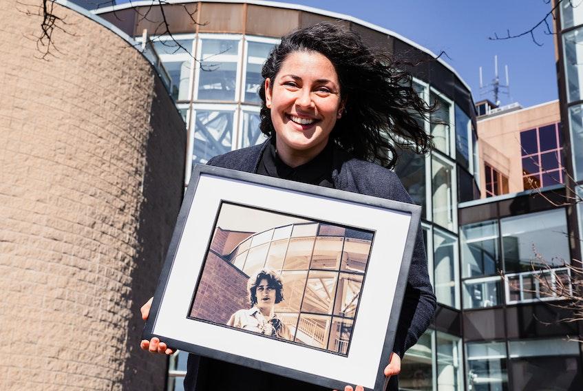 March 5 2021 -- Artistic Director Kat McCormack poses outside Alderney Landing Theatre's rotunda lobby with a photo of EFT's founding Artistic Director, Mary Vingoe, captured in the same spot by Ken Lam 22 years earlier. - James MacLean