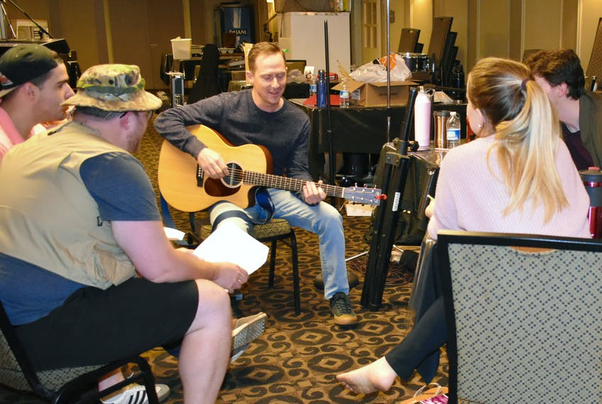 Mike Allison, the writer of We Are the Champions, teaching the cast harmonies from the gentle strum of his guitar.
