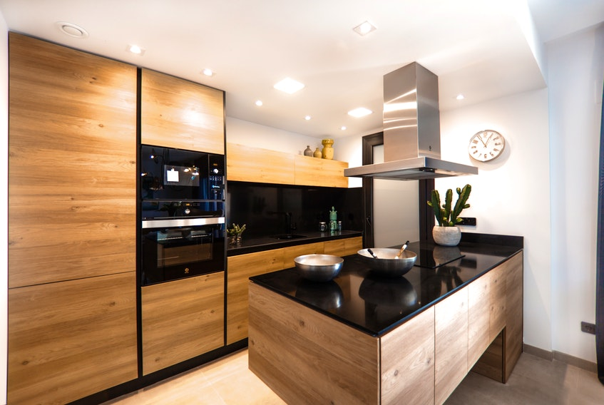 Wooden cabinets and dark countertops are some of the latest kitchen design trends. - Photo Courtesy Ralph Ravi Kayden.