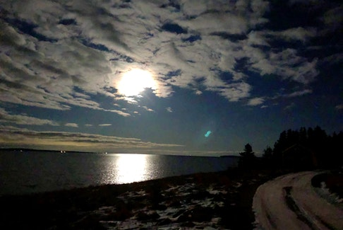 The second full moon of the year, the Full Wolf Moon, was shining down on Big Tancook Island when Lucy Neatby snapped this photo.  The mid-level altocumulus clouds added to the moonbeam magic.