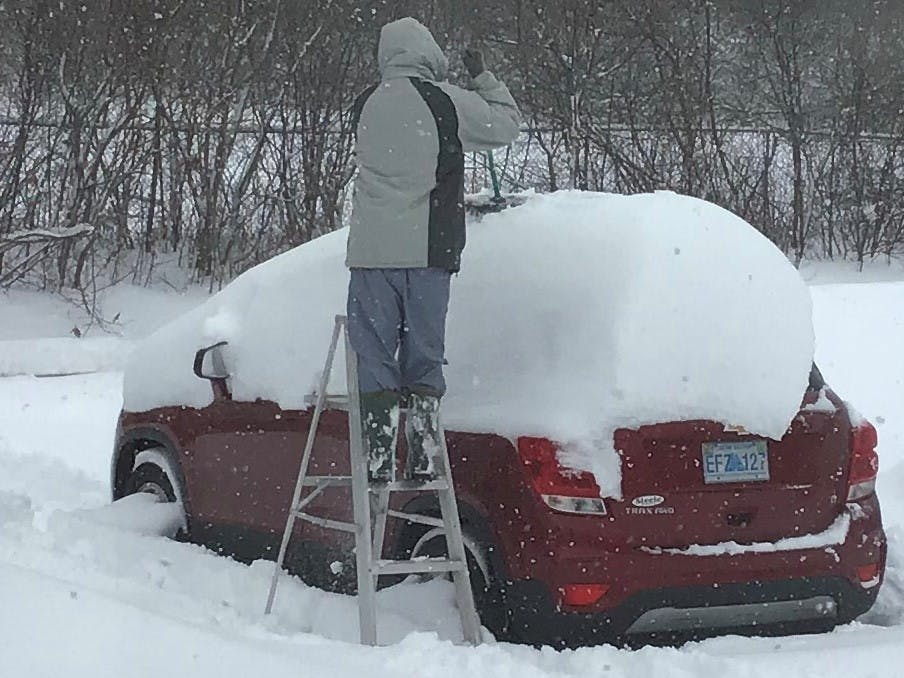 """Karen Watson's job was to take this fun photo of her husband, Bob, cleaning off the car following a significant """"dump"""" in Kentville, NS, earlier this month.  No word on whether Bob thought his job was fun!  There was so much snow he decided that a ladder would make the job a little easier.  Did the Watsons' wait until the plow was nearby?"""