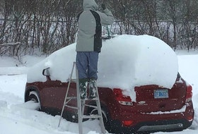 "Karen Watson's job was to take this fun photo of her husband, Bob, cleaning off the car following a significant ""dump"" in Kentville, NS, earlier this month.  No word on whether Bob thought his job was fun!  There was so much snow he decided that a ladder would make the job a little easier.  Did the Watsons' wait until the plow was nearby?"