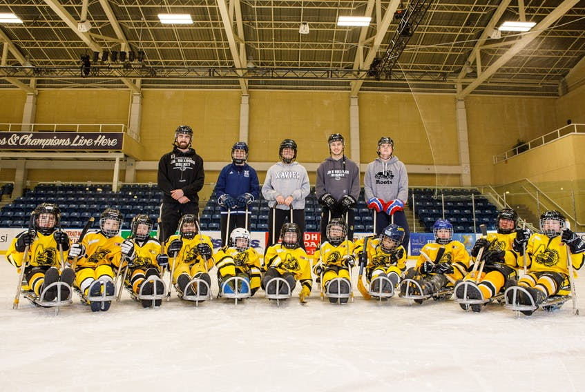 Gio Akeson, left, and other volunteers have stepped up in Antigonish to provide young athletes with an opportunity to play sledge hockey.