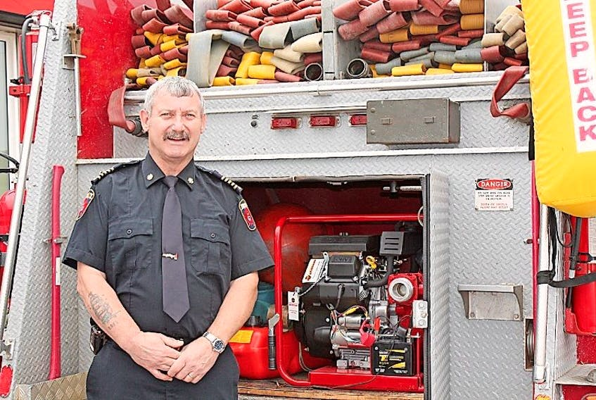 Fire chief Glen Hann proudly displays the department's new pump.
