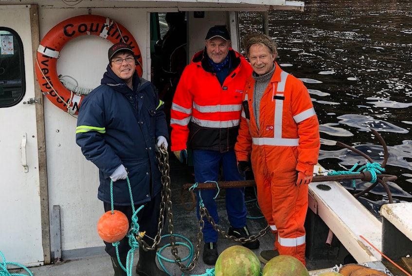 Asle Guneriussen (centre), aquaculture technician from the Norwegian company Akvaplan AS, leads an environmental assessment at a proposed aquaculture site near Burgeo, supported by fisherman Shawn Bowles and Burgeo resident Ken Benoit.