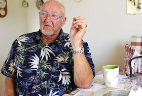 Bobbie Green sits at his kitchen table next to newspaper clippings about the 1973 mining explosion in Glace Bay. Green was one of six men injured in the flash fire.