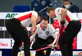 Nova Scotia skip Scott McDonald peers over the shoulders of Team Canada skip Brad Gushue as Canada's Brett Gallant, left, and Geoff Walker keep the ice clean at the 2021 Tim Hortons Brier Tuesday night in Calgary. Canada won 8-6. Michael Burns photo/Curling Canada