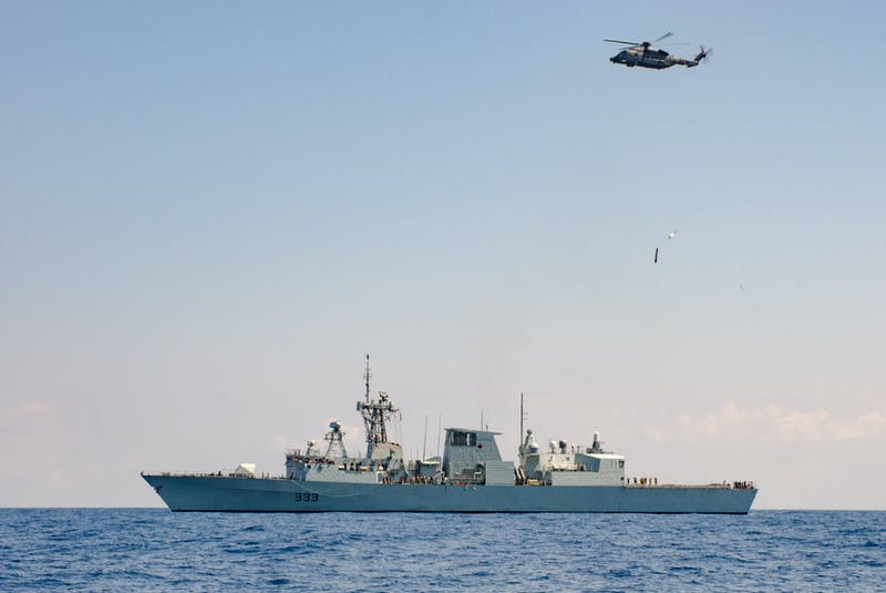 A CH-148 Cyclone helicopter releases a MK 46 Hydrodynamic Operational Training Torpedo (HOTTTORP), 200 yards of the port side of HMCS TORONTO, for the first ever Cyclone torpedo drop performed by an operational crew at sea brining the CH-148 Cyclone to full Anti-Submarine Warfare status, in the Mediterranean Sea during Operation REASSURANCE, April 19, 2019.Photo:  Lt(N) Simon Hardman, HMCS TORONTO / Canadian Forces Combat Camera