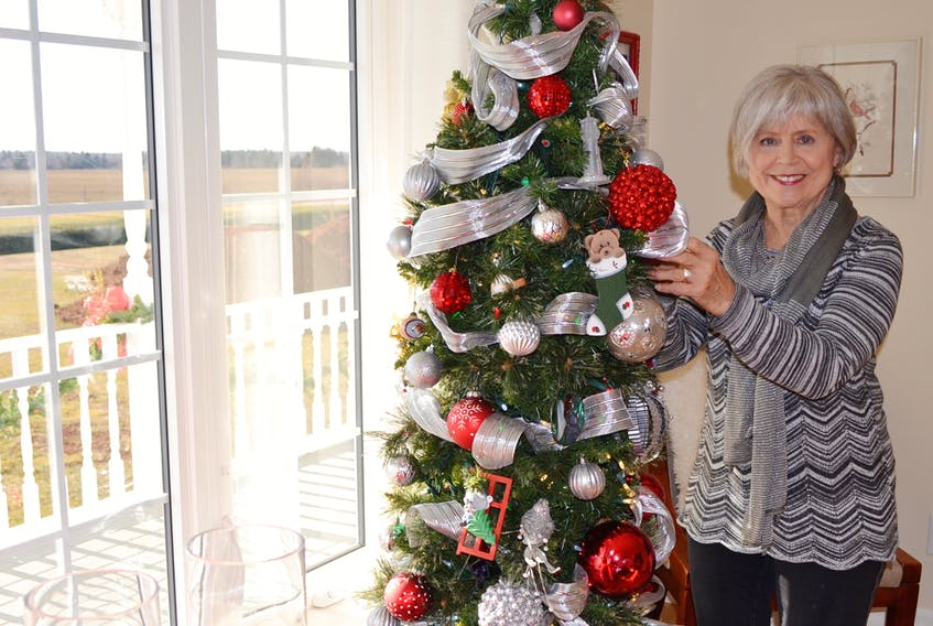 Irene Mallett adds some finishing touches to her decorating in preparation for the St. Anthony's Parish Christmas house tour today. ERIC MCCARTHY/JOURNAL PIONEER