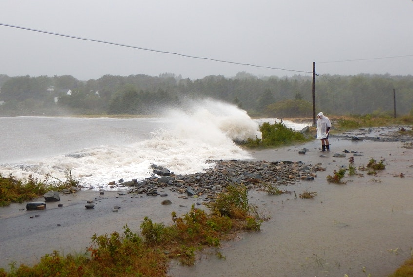 John DeMont, seen in a white raincoat, was about to be slammed by a wave from hurricane Dorian in 2019 on the South Shore.