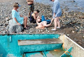 Ruthanna O'Brien sits beside Colin Greene on Jimtown beach, Antigonish County, after the pair were rescued.