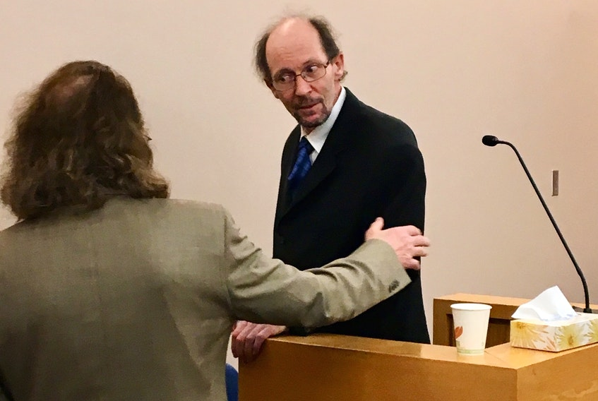 Kenneth Harrison (right) speaks with his lawyer Bob Buckingham during his trial Friday at provincial court in St. John's. Harrison collapsed on the stand during his testimony.