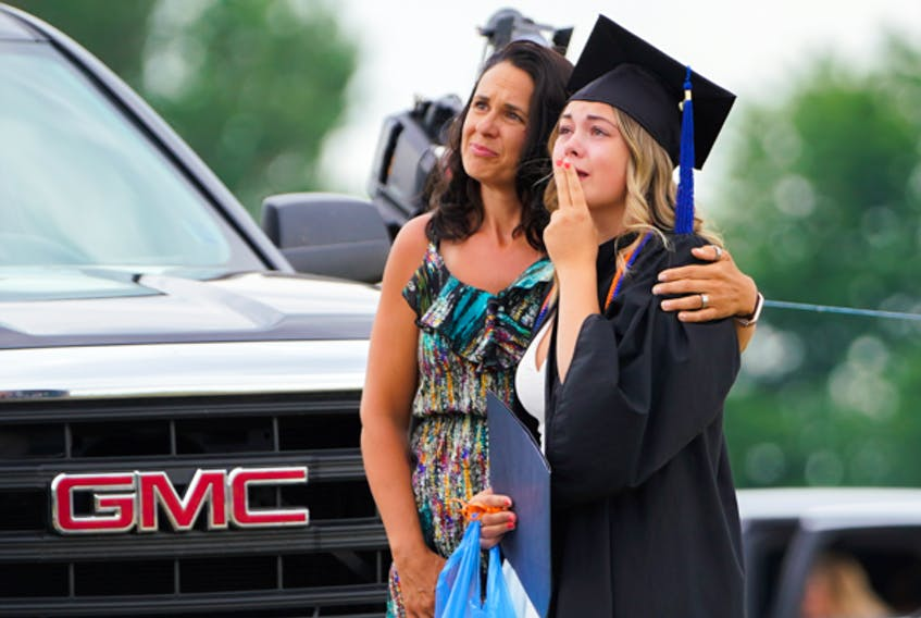 Jeannine Garett and her daughter Ameilia McLeod express their emotions while watching a tribute of Ameilia's father Sean McLeod during the Cobequid Educational Centre's outdoor graduation ceremony on Friday night (June 26) at the Lorraine farm in Upper Onslow. Ameilia's father and her stepmother Alanna Jenkins were among the 22 people who died during the mass shootings on April 18 and 19. A tribute was also played for shooting victim Emily Tuck, who would have been among the graduating class.