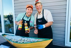 Jason Henzell, left, and Nolan D'Eon serve up fresh oysters from DEon Oyster Company in Eel Lake, Yarmouth County, with Henzell's sweet or sour oyster sauce, at an event at the West Pubnico Golf & Country Club, hosted as part of the Yarmouth Seafood and Wine Extravaganza with a Jamaican twist. Henzell owns restaurants and a resort in Jamaica.