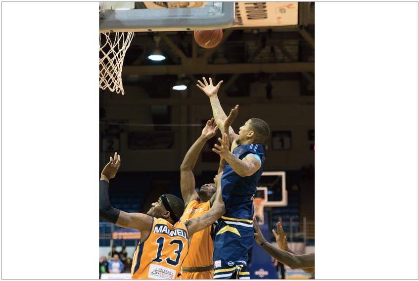 Island Storm/Stephene Poirier — Jarion Henry of the St. John's Edge (right) goes high to grab a rebound among Island Storm defenders, including Du'Vaughm Maxwell (13), in Charlottetown, P.E.I., Saturday. The Edge won their inaugural game, shading the Storm 97-96.