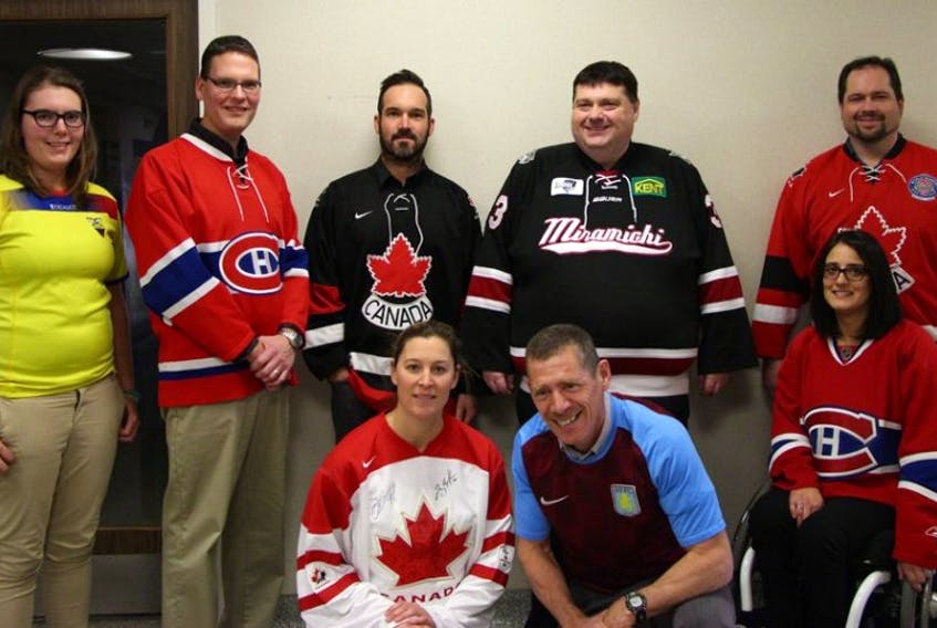 New Brunswickers are encouraged to participate in Jersey Day, Friday, Nov. 20, and RBC Sports Day in Canada, on Saturday, Nov. 21. Jersey Day is an opportunity to show your love and support for sport by wearing a jersey, team or club uniform to school, work or play. RBC Sports Day in Canada is a celebration of sport, from grassroots to high-performance, and an opportunity to celebrate the power of sport to build community and get Canadians moving. Front row, from left: Christine Powers-Tomsons, Steve Harris and Sabrina Durepos, consultants, sport and recreation branch, Department of Tourism, Heritage and Culture. Back row, from left: Brittany Pye, student intern at the department; Jamie Shanks and Jason Arseneault, consultants, sport and recreation branch; Tourism, Heritage and Culture Minister Bill Fraser; and Jeffrey LeBlanc, director of the sport and recreation branch.