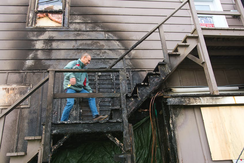 John MacKay of MacKay Real Estate climbs the charred stairs to the apartments above his office to see the damage caused by a fire Thursday night.
