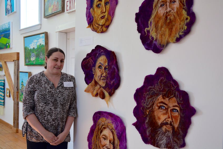 Artist Tacha Reed next to her latest project, Stewards, fibre portraits of Hants County artists and activists at the Avon River Heritage Society Museum During the 21st annual Great Little Art Show, which wrapped up on May 26.