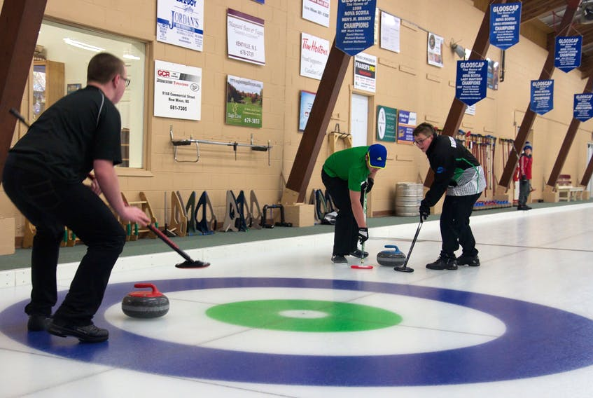 A team of U14 curlers sweep as the rock makes its way down the ice at the eighth annual Earl MacKinnon Classic Jan. 21 at the Glooscap Curling Club in Kentville.
