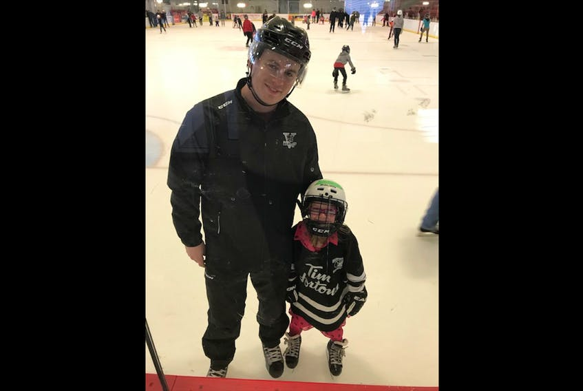 Drew Packman helps a young skater on the ice.