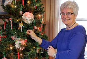 Karen Price, of Lockhartville Road, hangs a handmade ribbon candy ornament on the tree. She's found great success in creating these clay ornaments this year. CAROLE MORRIS-UNDERHILL