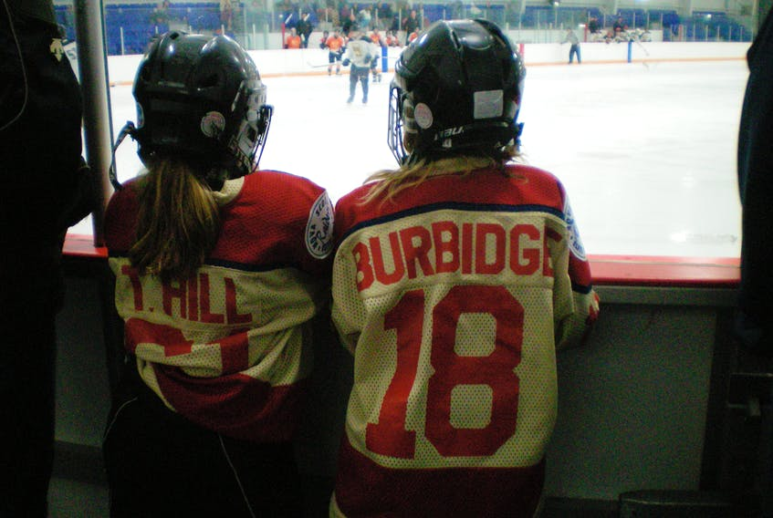 Tiffany Hill and Maggy Burbidge, seen watching hockey together when they were much younger. Their bond through hockey is strong as they approach the 2017 U18 National Tournament in Quebec.
